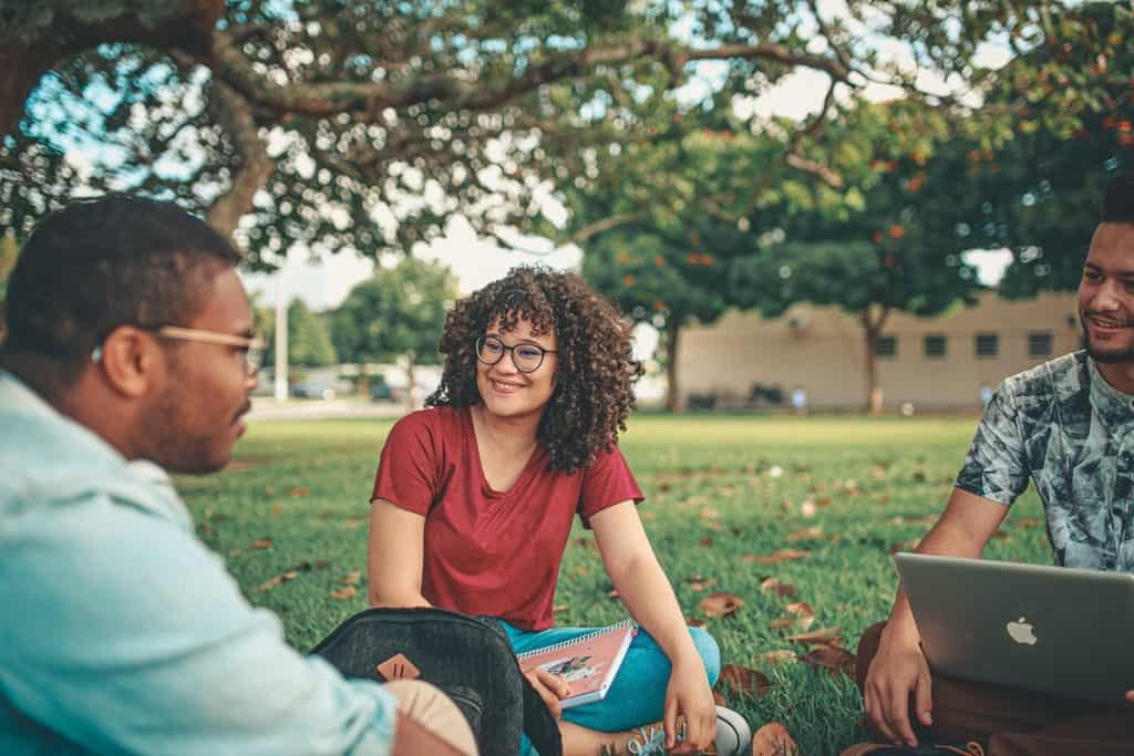 Group of critical thinking students sat outside